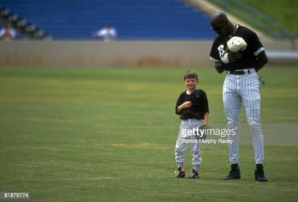 Minor League Baseball: Basketball player Birmingham Barons Michael Jordan on field with child fan Seth Garrett during anthem before game, Birmingham,...