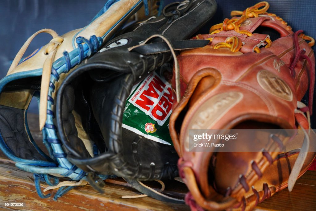 Closeup view of fielding gloves in dugout before New Hampshire