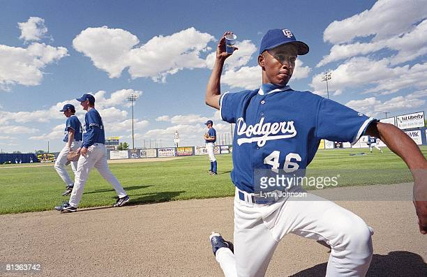 Minor League Baseball Great Falls Dodgers Andres Astacio practicing pitching grip and finger curve ball positioning with paper cup before game Great...