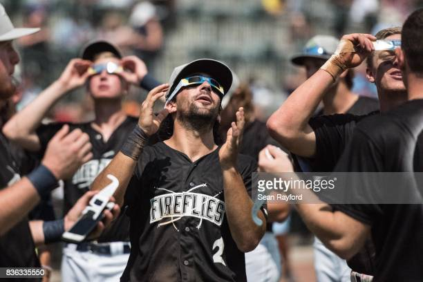 Minor league baseball player J.J. Franco watches the eclipse with teammates during a break in the game at Spirit Communications Park August 21, 2017...