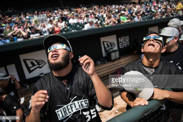 Minor league baseball player Jose Medina looks to the sun during a solar eclipse at Spirit Communications Park August 21, 2017 in Columbia, South...