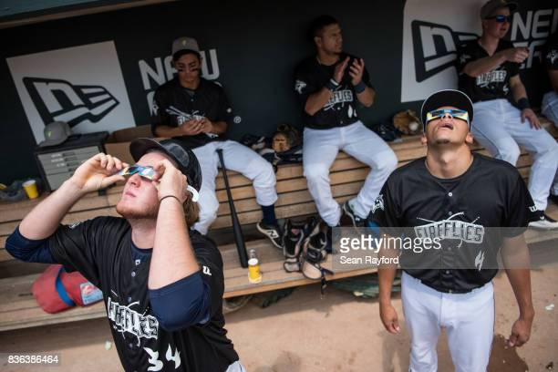 Minor league baseball players Dash Winningham and Justin Brantley , with the Columbia Fireflies, watch a solar eclipse at Spirit Communications Park...