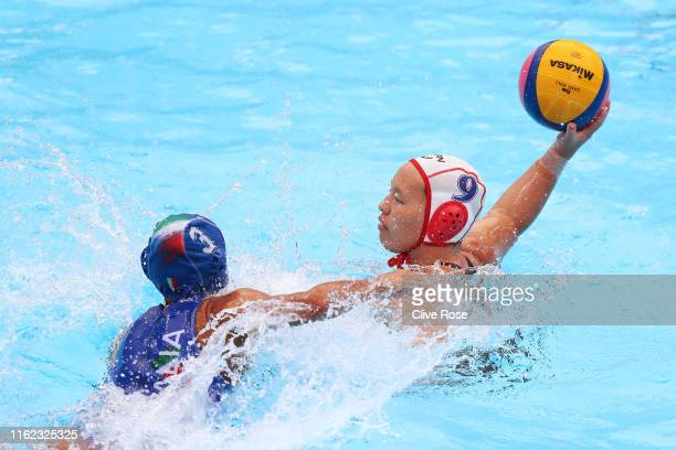 Minori Yamamoto of Japan takes a shot against Arianna Garibotti of Italy during their Women's Water Polo Preliminary round match on day four of the...
