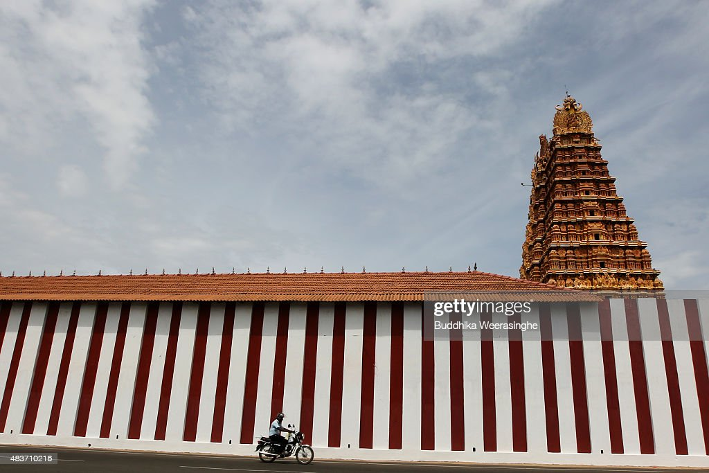 Minority ethnic Tamil man rides his bike past the temple wall on August 12,2015 in Jaffna, Sri Lanka. The UN's Human Rights Council investigation into alleged war crimes committed by both the Sri Lankan Government and the Liberation Tigers of Tamil Eelam (LTTE) during the Sri Lankan Civil War is due to be released in September.