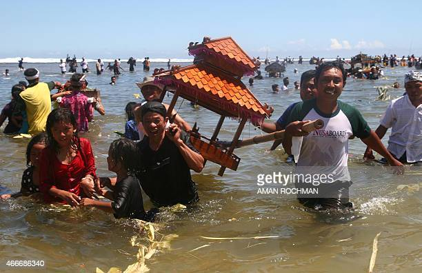 Minority Indonesian Hindu worshippers carry offerings during the Melasti ceremony prayer at the coast of Malang in eastern Java island on March 18...