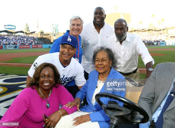 Minority owner of the Los Angeles Dodgers Magic Johnson poses for a photo with the family of Jackie Robinson and manager Dave Roberts of the Los...