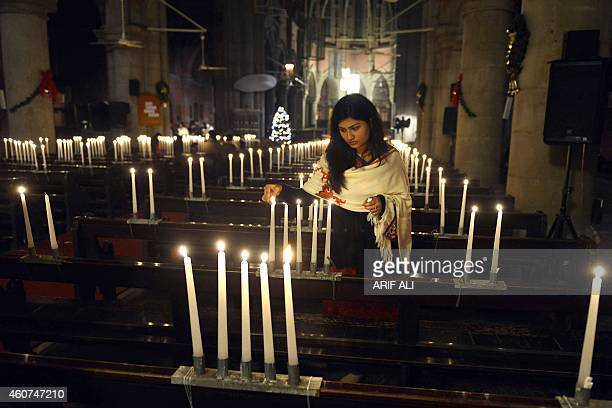 A minority Pakistani Christian lights candles before a preChristmas Sunday service where they prayed for the victims of the Peshawar school massacre...
