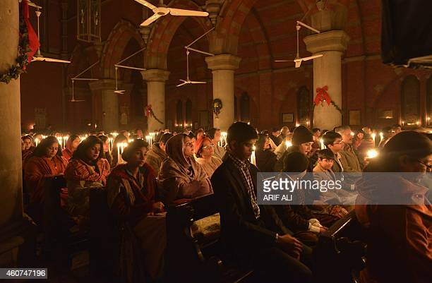 Minority Pakistani Christians seen gathered during a preChristmas Sunday service by candlelight pray for the victims of the Peshawar school massacre...