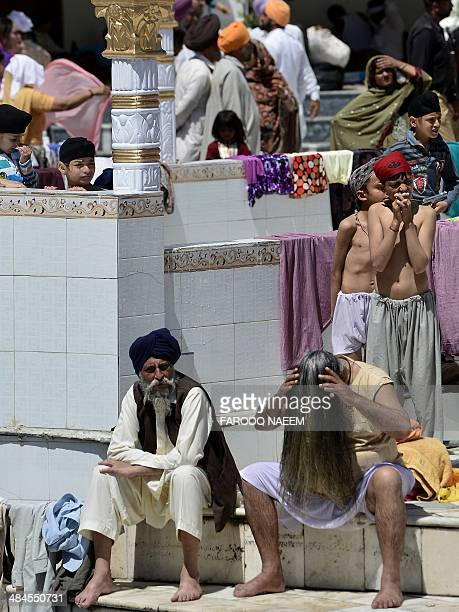 A minority Pakistani Sikh devotee dries his hair after taking a holy dip at the Gurdwara Punja Sahib in Hasan Abdal the third most sacred city for...