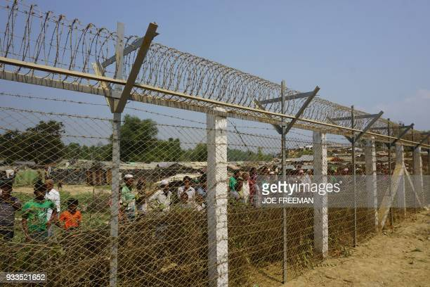 Minority Rohingya Muslims gather behind Myanmar's border lined with barbed wire fences in Maungdaw district located in Rakhine State bounded by...