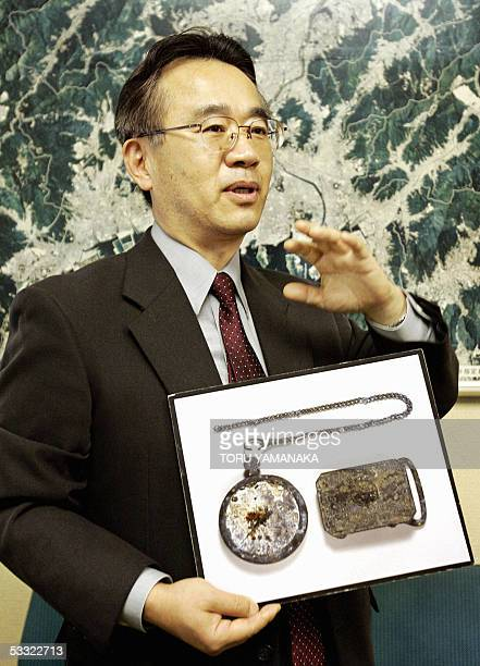 Minoru Hataguchi director of the Hiroshima Peace Memorial Museum speaks to an AFP reporter as he holds a photo of a burned buckle and a pocket watch...
