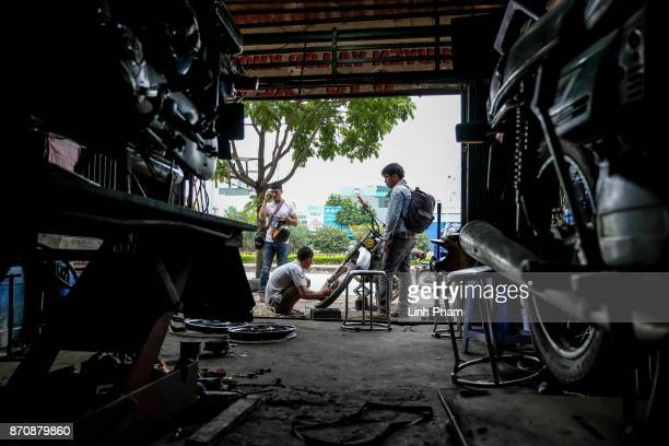 Minsk motorcycle enthusiast repairs his tire while on the way to the offroad race on November 5 2017 in Hanoi Vietnam A new generation of Vietnamese...