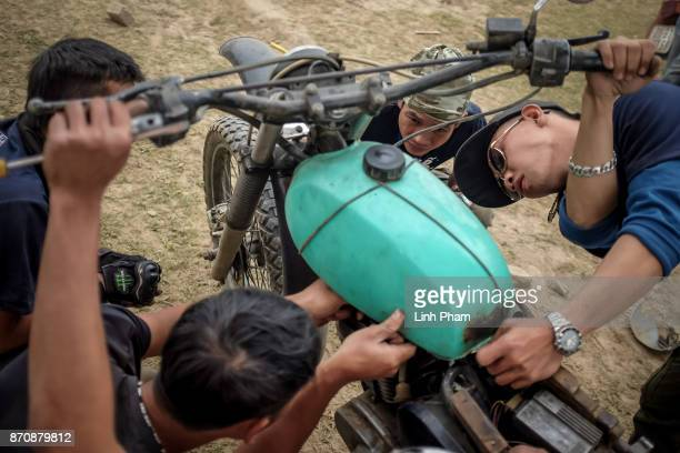Minsk motorcycle enthusiasts help each others finetuning and fixing their vehicles before the offroad race on November 5 2017 in Hanoi Vietnam A new...