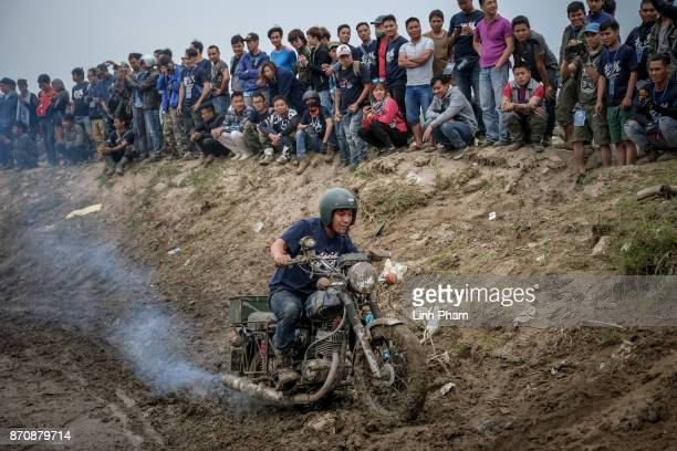 Minsk motorcyclist tries try to get over the dirt slope at an offroad race on November 5 2017 in Hanoi Vietnam A new generation of Vietnamese have...