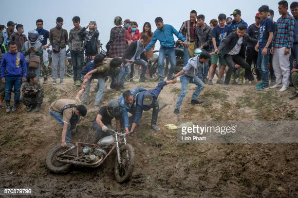 Minsk motorcyclist tries try to get over the dirt slope with the help of audiences at an offroad race on November 5 2017 in Hanoi Vietnam A new...
