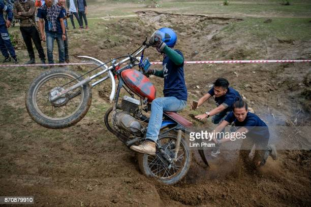 Minsk motorcyclist tries try to get over the dirt slope with the help from audiences at an offroad race on November 5 2017 in Hanoi Vietnam A new...