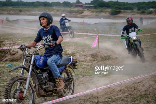Minsk motorcyclists race at a dirt track on November 5 2017 in Hanoi Vietnam A new generation of Vietnamese have started to ply the roads across...