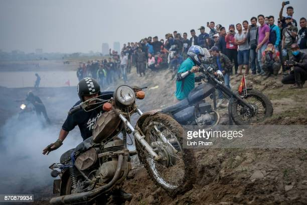 Minsk motorcyclists try to get over the dirt slope at an offroad race on November 5 2017 in Hanoi Vietnam A new generation of Vietnamese have started...