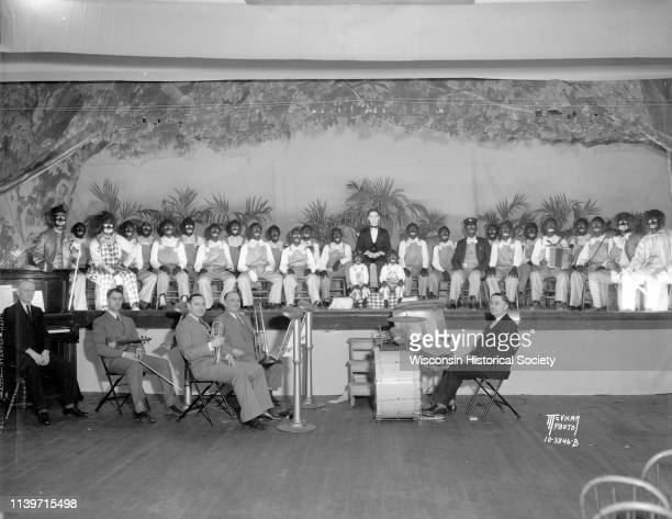 Minstrel show actors seated on stage in costume and black face with small orchestra seated below at Luther Memorial Church 1023 University Avenue...