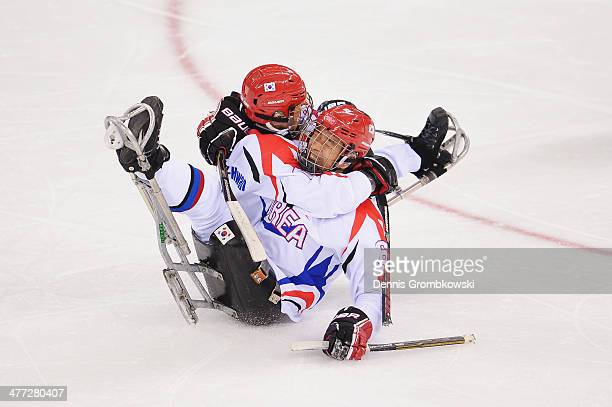 MinSu Han of Korea celebrates with team mate SeungHwan Jung after scoring his team's first goal during the Ice Sledge Hockey Preliminary Round Group...