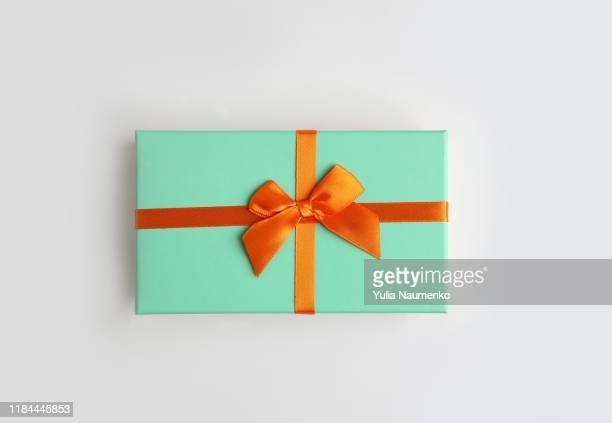 mint color gift box with orange ribbon on white background. isolate, copy space. - cadeau photos et images de collection