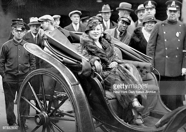 Minus $20000 in jewels of which she was robbed in Hollywood Mae West arrives at Grand Central in a carriage