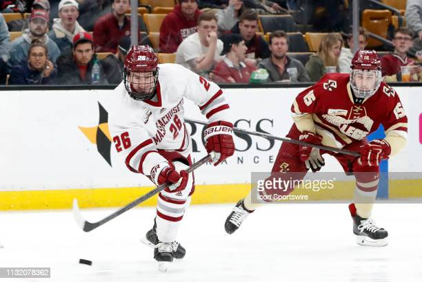 Minutemen defenseman Colin Felix plays a pass chased by Boston College Eagles forward JD Dudek during a Hockey East semifinal game between the Boston...