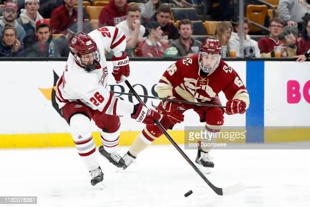 Minutemen defenseman Colin Felix slips away from Boston College Eagles forward JD Dudek during a Hockey East semifinal game between the Boston...