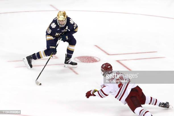 Minutemen defenseman Jake McLaughlin dives in to stop Notre Dame Fighting Irish forward Jack Jenkins during the Northeast Regional final between the...