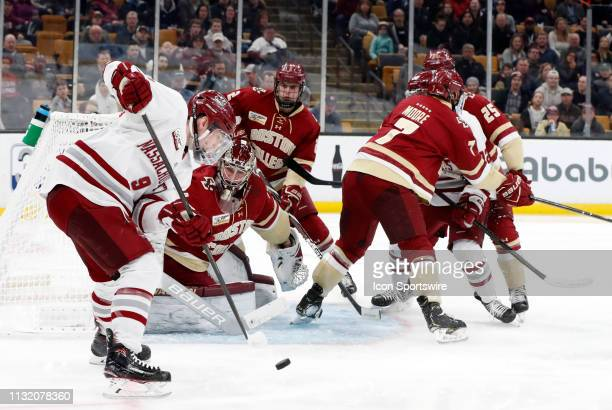 Minutemen forward John Leonard tries to get the handle with Boston College Eagles goaltender Joseph Woll looking on during a Hockey East semifinal...