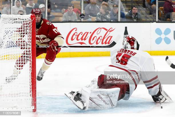 Minutemen goalie Filip Lindberg deflects a shot watched by Boston College Eagles forward David Cotton during a Hockey East semifinal game between the...