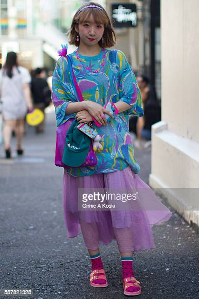 Miochin carrying a pink and blue shark iPhone case is seen on Harajuku St wearing a vintage shirt and skirt watermelon socks and is decked out in...