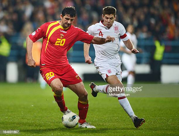 Miodrag Dzudovic of Montenegro battles with Steven Gerrard of England during the FIFA 2014 World Cup Qualifier Group H match between Montenegro and...