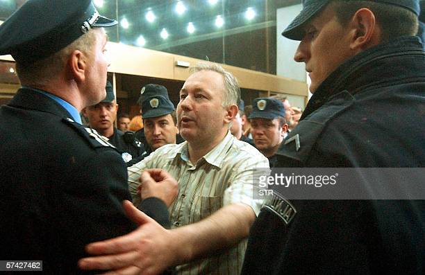 Miodrag Popov editor in chief talks to police officers guarding the entrance of BK television station building in Belgrade early 26 April 2006 The...