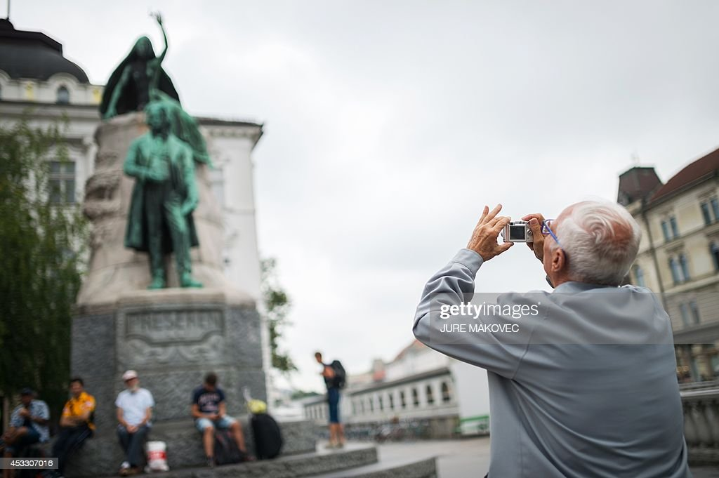 Miquel Ribas, an 82-year old Spaniard, takes a picture as he visits Ljubljana on July 28, 2014, during a week-long trip to Slovenia. Ribas, who lives in a care home in Mataro, on the Spanish coast near Barcelona, has free accommodation during his trip in a similar care home in Topolsica, Slovenia, provided by Jozica Kucera, a 77-year-old Slovenian widow, who will spend the same time in his room in Spain. This is the first international exchange of rooms in care homes for seniors, organized by social networking agency Linkedage, a Slovenian company that developed a web platform to link residences all over Europe and the world to enable similar exchanges or to rent vacant rooms.