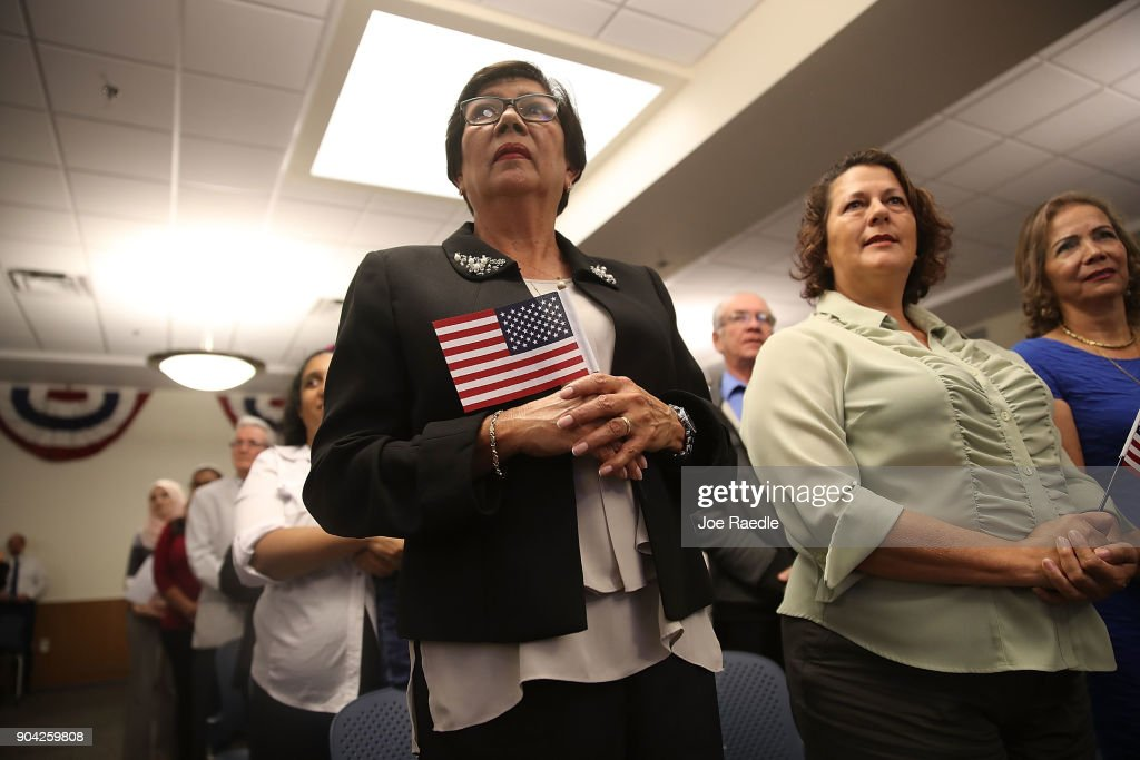 Mira Delgado (L), orginally from Nicaragua, and others become American citizens during a U.S. Citizenship & Immigration Services naturalization ceremony at the Hialeah Field Office on January 12, 2018 in Hialeah, Florida. 150 people from different countries around the world took part in the Oath of Allegiance.