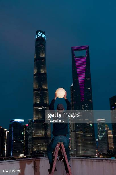miracle concept photo:one asian male holding a moon waiting for fairy story happen in night city - ladder to the moon stock pictures, royalty-free photos & images