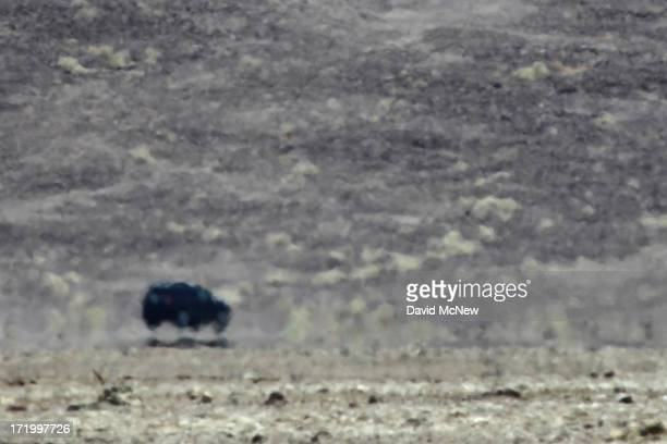 A mirage makes a car appear as if it's flying as a heat wave spreads across the American West on June 30 2013 in Death Valley National Park...