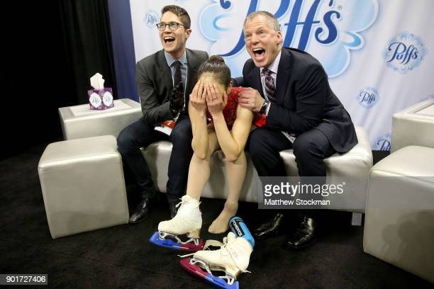 Mirai Nagasu celebrates in the kiss and cry with coaches Drew Meekins and Tom Zakrajsek after skating in the Ladies Free Skate during the 2018...