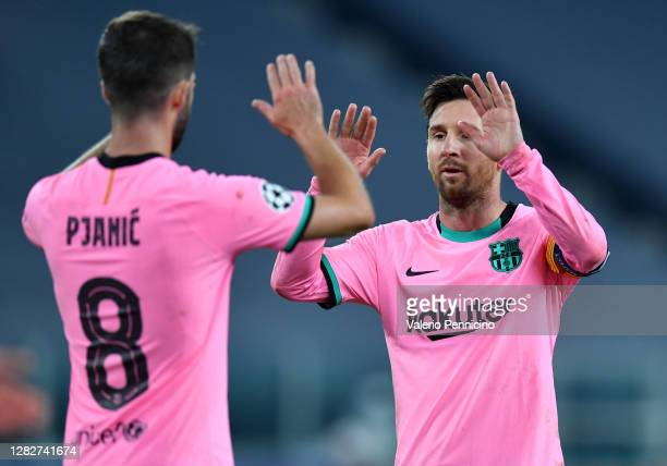 Miralem Pjanic and Lionel Messi of Barcelona high five during the UEFA Champions League Group G stage match between Juventus and FC Barcelona at...