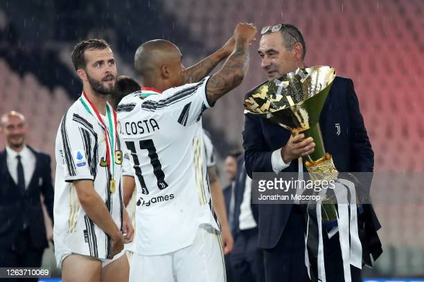 Miralem Pjanic looks on as Douglas Costa of Juventus positions Maurizio Sarri Head coach's spectacles as he holds the Scudetto following the Serie A...