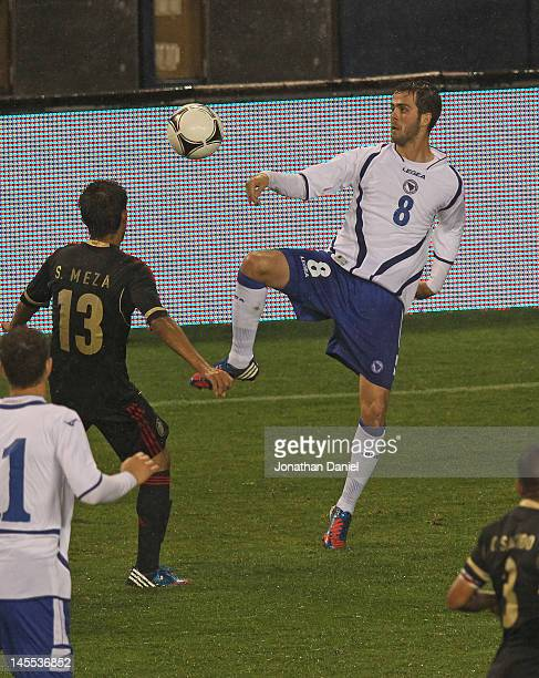 Miralem Pjanic of BosniaHerzegovina passes around Severo Meza of Mexico during an international friendly at Soldier Field on May 31 2012 in Chicago...