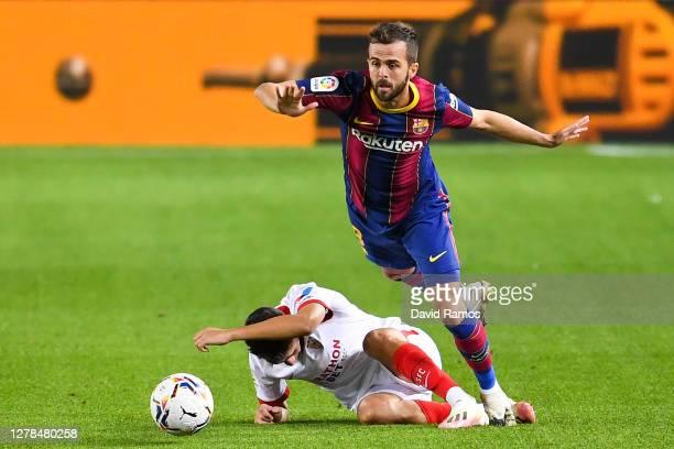Miralem Pjanic of FC Barcelona competes for the ball with Munir El Haddadi of Sevilla FC during the La Liga Santander match between FC Barcelona and...