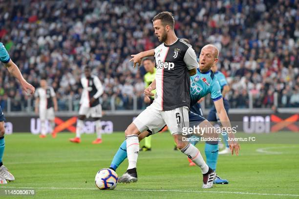 Miralem Pjanic of Juventus competes for the ball with Andrea Masiello of Atalanta BC during the Serie A match between Juventus and Atalanta BC on May...