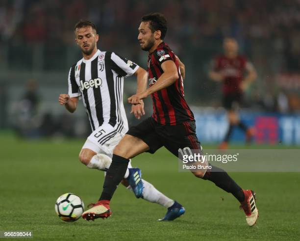 Miralem Pjanic of Juventus competes for the ball with Hakan Calhanoglu of AC Milan during the TIM Cup Final between Juventus and AC Milan at Stadio...