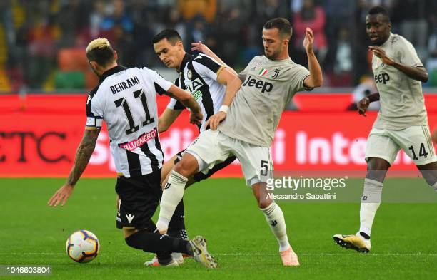 Miralem Pjanic of Juventus competes for the ball with Kevin Lasagna of Udinese Calcio during the Serie A match between Udinese and Juventus at Stadio...