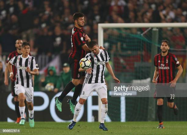 Miralem Pjanic of Juventus competes for the ball with Patrick Cutrone of AC Milan during the TIM Cup Final between Juventus and AC Milan at Stadio...
