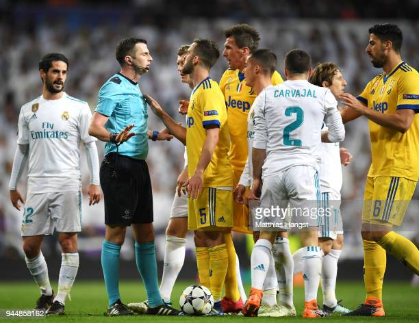 Miralem Pjanic of Juventus confronts referee Michael Oliver during the UEFA Champions League Quarter Final Second Leg match between Real Madrid and...
