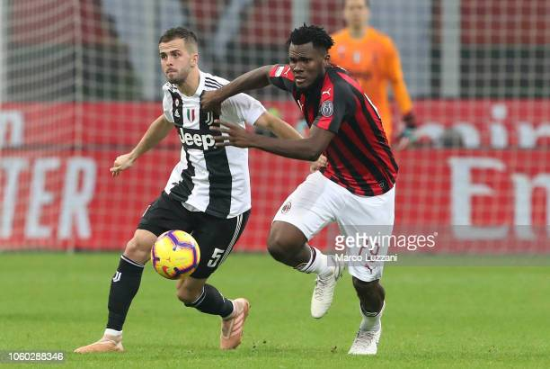 Miralem Pjanic of Juventus FC competes for the ball with Franck Kessie of AC Milan during the Serie A match between AC Milan and Juventus at Stadio...