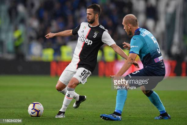 Miralem Pjanic of Juventus is challenged by Andrea Masiello of Atalanta during the Serie A match between Juventus and Atalanta BC on May 19 2019 in...